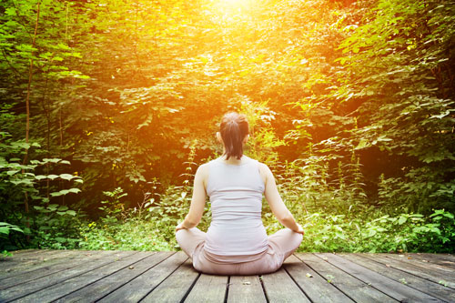 How-Being-in-Nature-Helps-You - woman sitting meditating facing woods