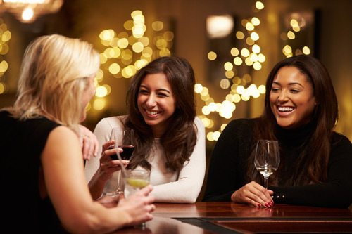 3 women having drinks at bar