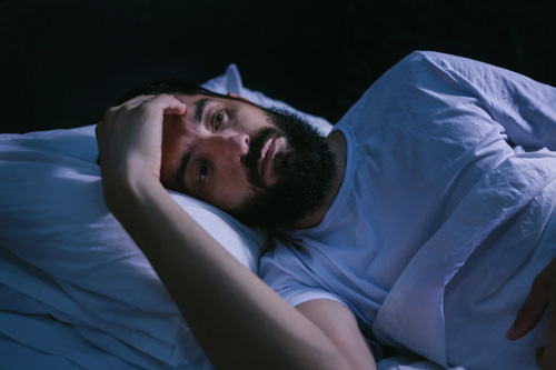 man wide awake at night in bed