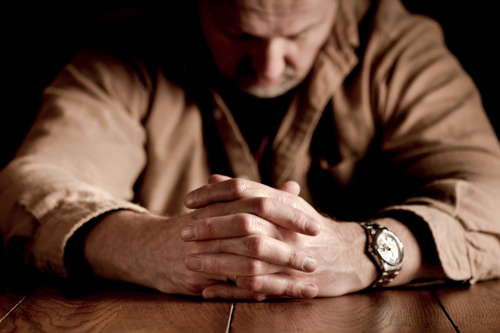 older man sitting at table with hands clasped and head down - men