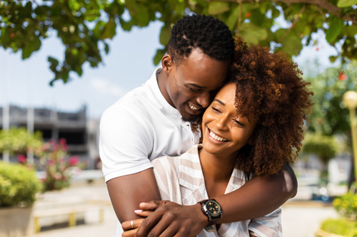 beautiful happy African American couple embracing outdoors - romance