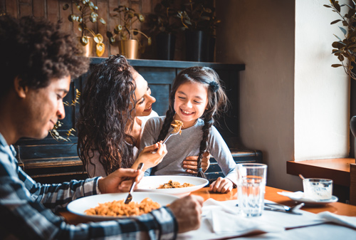 young Hispanic family at table enjoying meal together - parenting