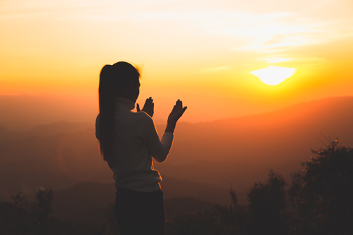 woman on hill or mountain during sunset - spirituality