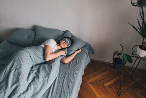 woman sleeping on bed with eye mask on - sleep habits