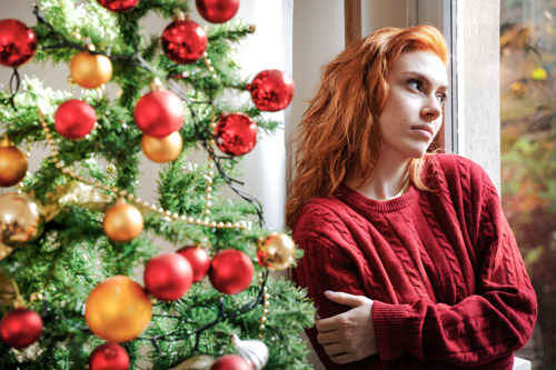 pretty young red haired woman looking out the window while standing next to Christmas tree - looking lonely - loneliness