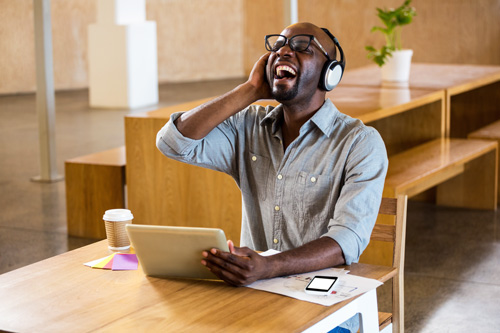 handsome black man using laptop and headphones is laughing