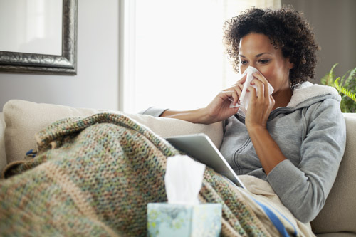 sick woman at home on couch blowing her nose into a tissue - immune system