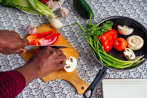 hands of Black man cutting up fresh vegetables - whole foods